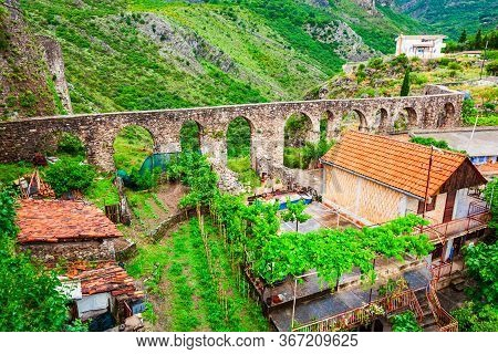 Medieval Aqueduct Ruins And Local Houses In The Stari Grad Bar Or Bar Old Town, A Small Town In Mont