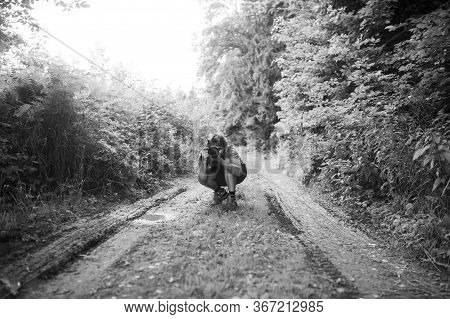 Black And White Image Of Young Man Kneeling Down On A Country Road Taking Photo With Dslr Camera Dir