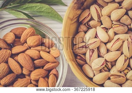 Almonds And Pistachios In Bowls Close-up. Dress Pistachios And Almond Kernels On A Light Background