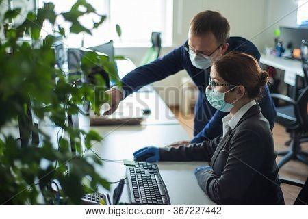 Colleagues Work In Surgical Masks In An Open Office Space Communicate At The Work Desk. A Male Top M
