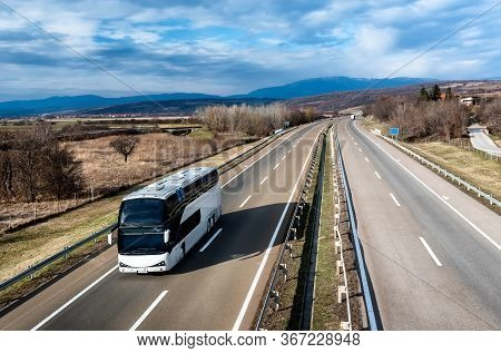 White Modern Comfortable Tourist Bus Driving Through Highway At Bright Sunny Sunset. Travel And Coac