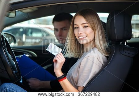 Joyful Girl Driving A Training Car With A Drivers License Card In Her Hands