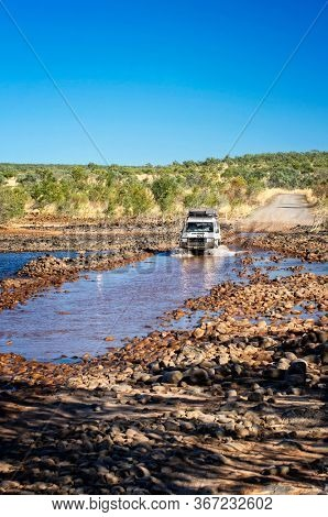 Western Australia – Dried out Pentecost river crossing at the Gibb River Road with 4WD vehicle at the morning light
