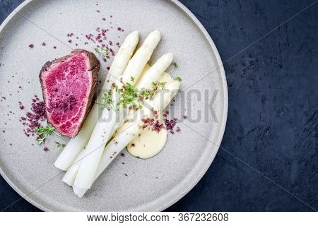 Barbecue dry aged wagyu beef fillet head medallion steak natural with white asparagus and sauce hollandaise as top view on a modern design plate with copy space left