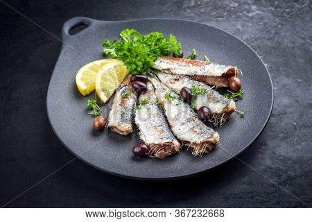 Fried sardines with lettuce and kalamata olives offered as closeup on a modern design plate with copy space
