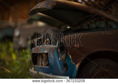 An Old Rusty Abandoned Car With An Open Hood