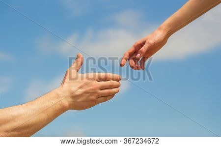 Giving A Helping Hand. Hands Of Man And Woman On Blue Sky Background. Lending A Helping Hand. Solida