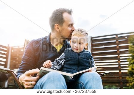 Father And Baby Boy Read A Book Outdoors Together, Daddy Is Kissing His Little Son Tenderly