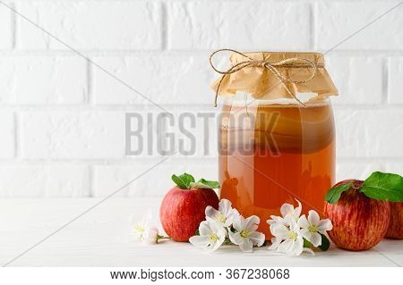 Homemade Fermented Kombucha In A Glass Jar And Red Apples On A Background Of A White Brick Wall. Kom