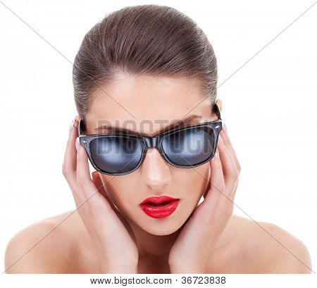 young woman with great sex appeal straightening her sunglasses