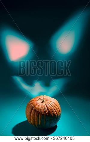 Halloween smile. Projection of glowing Halloween pumpkin lantern with Jack o'Lantern face on wall