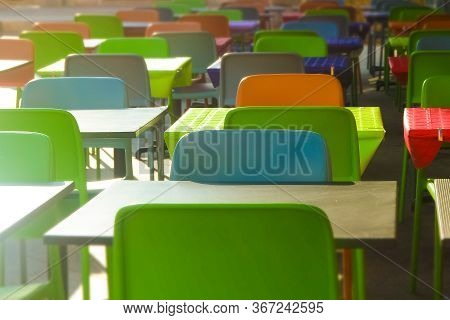 Rows Of Colored Plastic Empty Tables And Chairs. Empty Plase Without People. Financial And Economic
