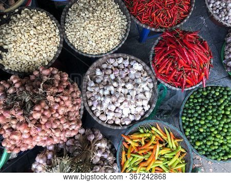 Top view on a large assortment of row loose vegetables and fruits for sale in a street. Short circuit production at Hue Market
