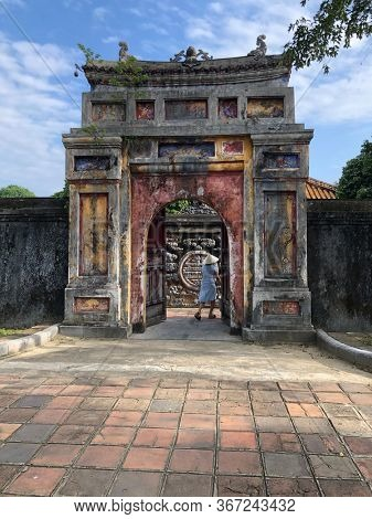 Woman walking through an old arch at  Imperial Minh Mang Tomb in Hue, Vietnam, Imperial City
