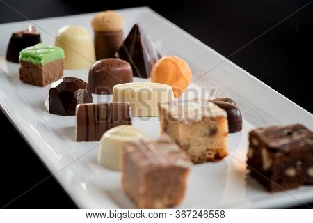 Mix Of Chocolates On A Table With Black Background, Confectioners Assortment Of Bon Bon Candies