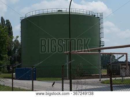 A Green Oil Tank In A Gated Oil Tank Farm
