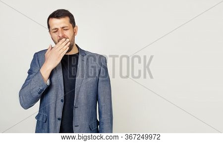 Business Man On An Isolated Background Bored Yawns Tired Hand Covering His Mouth. Anxiety And Drowsi