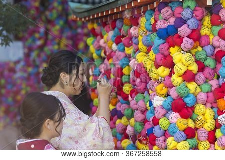 Kyoto, Japan - November, 8, 2019: Japanese Geisha Signing Colorful Temple Charm Formed As Colorful S