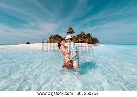 newlyweds are hugging on the background of a tropical island