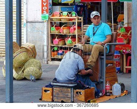 Cuenca, Ecuador - December 23, 2018: Unidentified Ecuadorian Man Shoe Shine Worker Cleans The Other