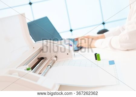 Young woman in the office of the printing company sets up a plotter for printing advertising brochures