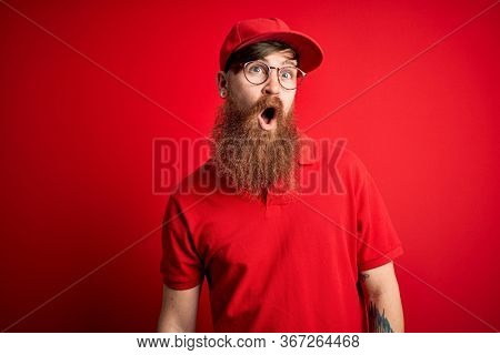 Young handsome delivery man wearing glasses and red cap over isolated background In shock face, looking skeptical and sarcastic, surprised with open mouth