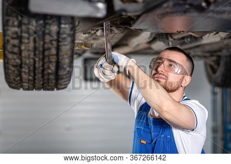 A Young Man Auto Mechanic In Overalls At His Workplace Repairs The Car's Suspension, Shines A Lanter