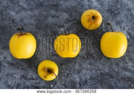 Plant-based Ingredients, Group Of Golden Delicious Apples With Smaller And Bigger Sizes On Concrete
