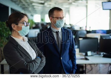 Colleagues In Protective Masks Work In An Open Space Office. A Man And A Woman In Suits Work At The