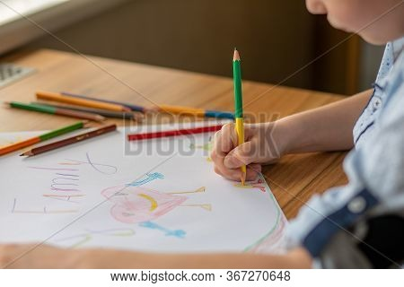The Child's Hand Holds A Pencil And Draws A Picture. The Inscription On The Drawing Is Family. On Th