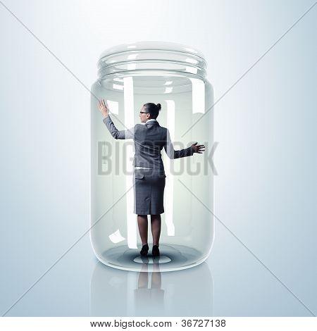 Businesswoman inside glass jar