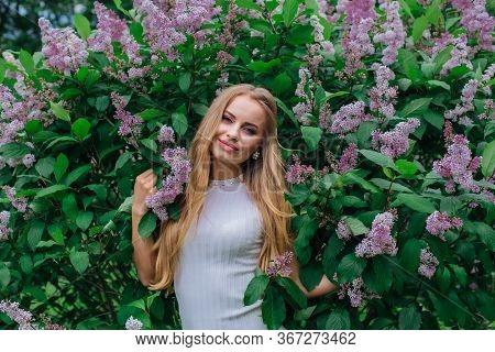 Portrait Of A Charming Blond Woman Wearing Beautiful White Dress Standing Next To Lilac Bush.