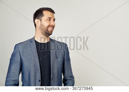 Closeup Of A Handsome Bearded Guy In A Jacket Standing In Profile, Looking To The Side, Posing For A