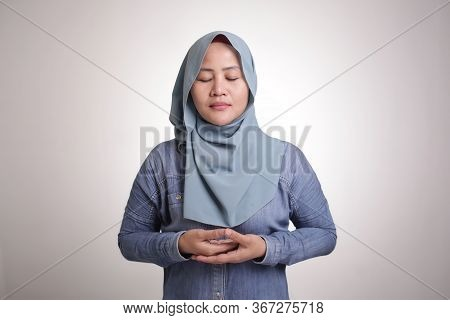 Portrait Of Asian Female Muslim Womman Wearing Hijab Doing Relaxing Yoga, Close Her Eyes And Smile,