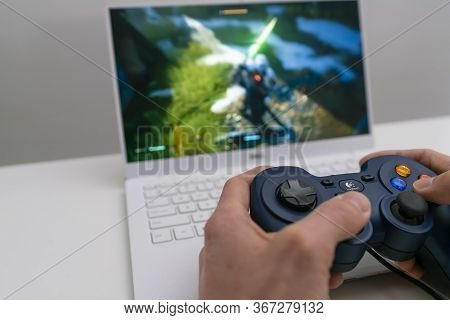 Melbourne, Australia - May 11, 2020: Playing Game On Laptop Computer With Joypad