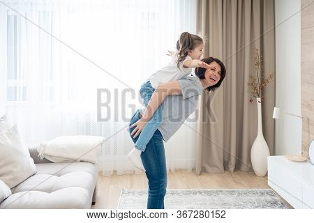 Happy Mother Giving Joyful Piggyback Ride To Her Daughter, Having Fun At Home, Single Mother Happy F