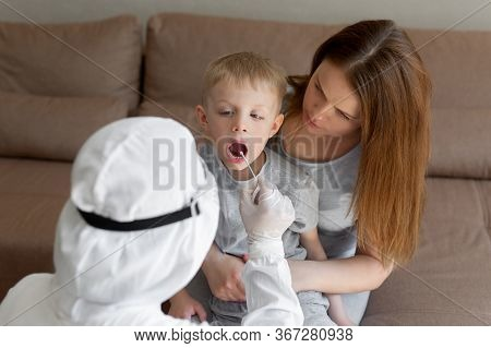 Doctor Takes A Cotton Bud From Child Mouth To Analyze The Saliva, Mucous Membrane For Dna Tests, Cov
