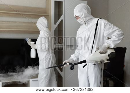Coronavirus Disinfection. People In Hazmats Making Disinfection In Flat, Copy Space, Hot Steam Disin