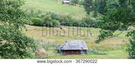 Rural Scene In Summer. Old Barn Wood And Haystack On Green Lands Of Ukrainian Village.