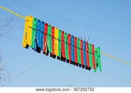 Multicolored Plastic Clothespins On Clothesline Rope Outdoor
