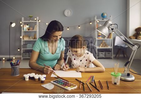 Happy Family. Little Girl And Mother Draw On The Table In The Room. Mom Teaches Daughter To Draw Whi