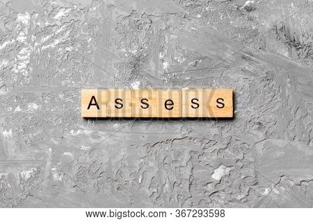 Assess Word Written On Wood Block. Assess Text On Cement Table For Your Desing, Concept