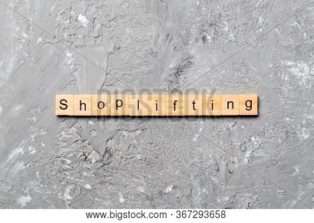 Shoplifting Word Written On Wood Block. Shoplifting Text On Cement Table For Your Desing, Top View C