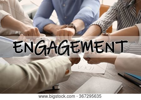 Engagement Concept. People Holding Fists Together Over Table, Closeup