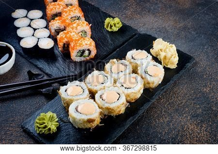 Tasty Sushi And Maki Rolls Set On Stone Plate With Sauces, Chopsticks, Ginger And Wasabi On Dark Tab
