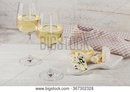 White Wine Served With Cheese Plate On Light Background. Two Wineglasses Of Vino Verde. Seasonal Hol