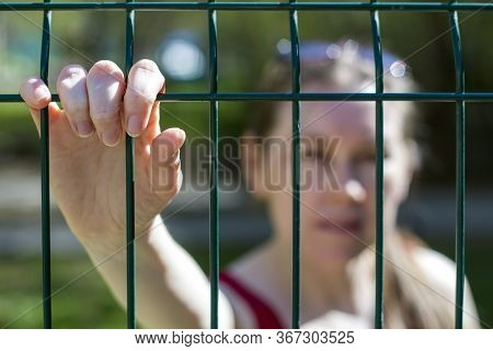 The Concept Of Closure Of The Border, Isolation. Inability To Leave. Female Hands On The Lattice As