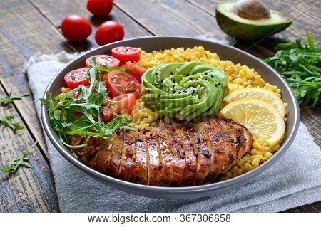 Bulgur With Grilled Chicken Breast, Fresh Vegetables, Avocado, Arugula. Diet Lunch On A Wooden Table