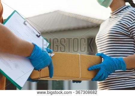 The Postman Wearing The Protective Gloves Deliver To Home.\nasian Woman Receiving Boxes From Postman