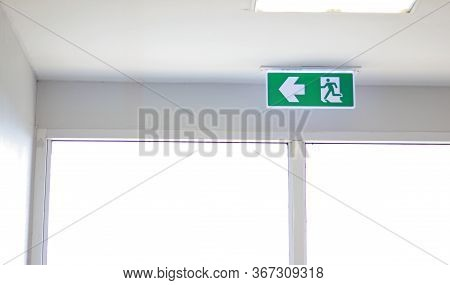 Fire Exit Sign On The Ceiling Entry The Fire Escape, Green Safety Light Symbol Isolated In White Win
